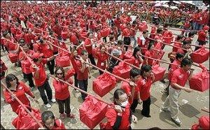 ผู้สนับสนุนทักษิณ ชินวัตร อย่างน้อย ๒๐,๐๐๐ คน กำลังเดินแบกกล่องซึ่งบรรจุรายชื่อผู้ร่วมลงนามถวายฎีกาผ่านถนนใกล้กับพระบรมมหาราชวัง เมื่อวันจันทร์ที ๑๗ สิงหาคม ๒๕๕๒