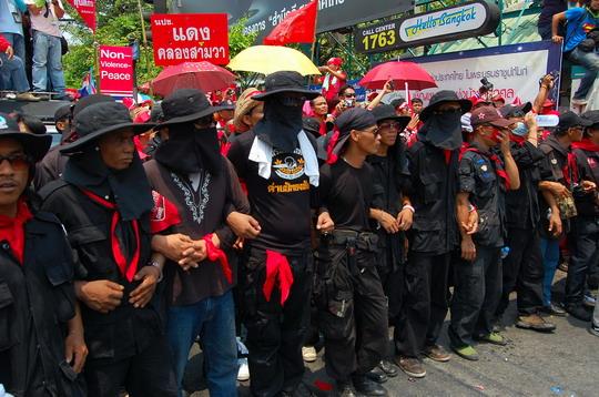ฝ่ายป้องกันในชุดดำคล้องแขนนำหน้าเพื่อควบคุมกลุ่มผู้ชุมนุม – ภาพโดย เนอร์มอล โกช
