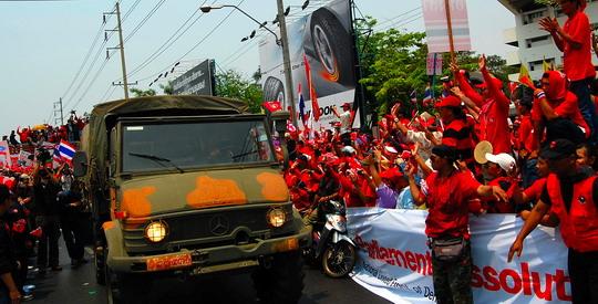 รถบรรทุกของทหารสามคันเคลื่อนออกไปตามทางที่เสื้อแดงแหวกให้ พร้อมกับเสียงไชโยโห่ร้องจากเสื้อแดง: เสียงเชียร์ดังสนั่น – ภาพโดย เนอร์มอล โกช